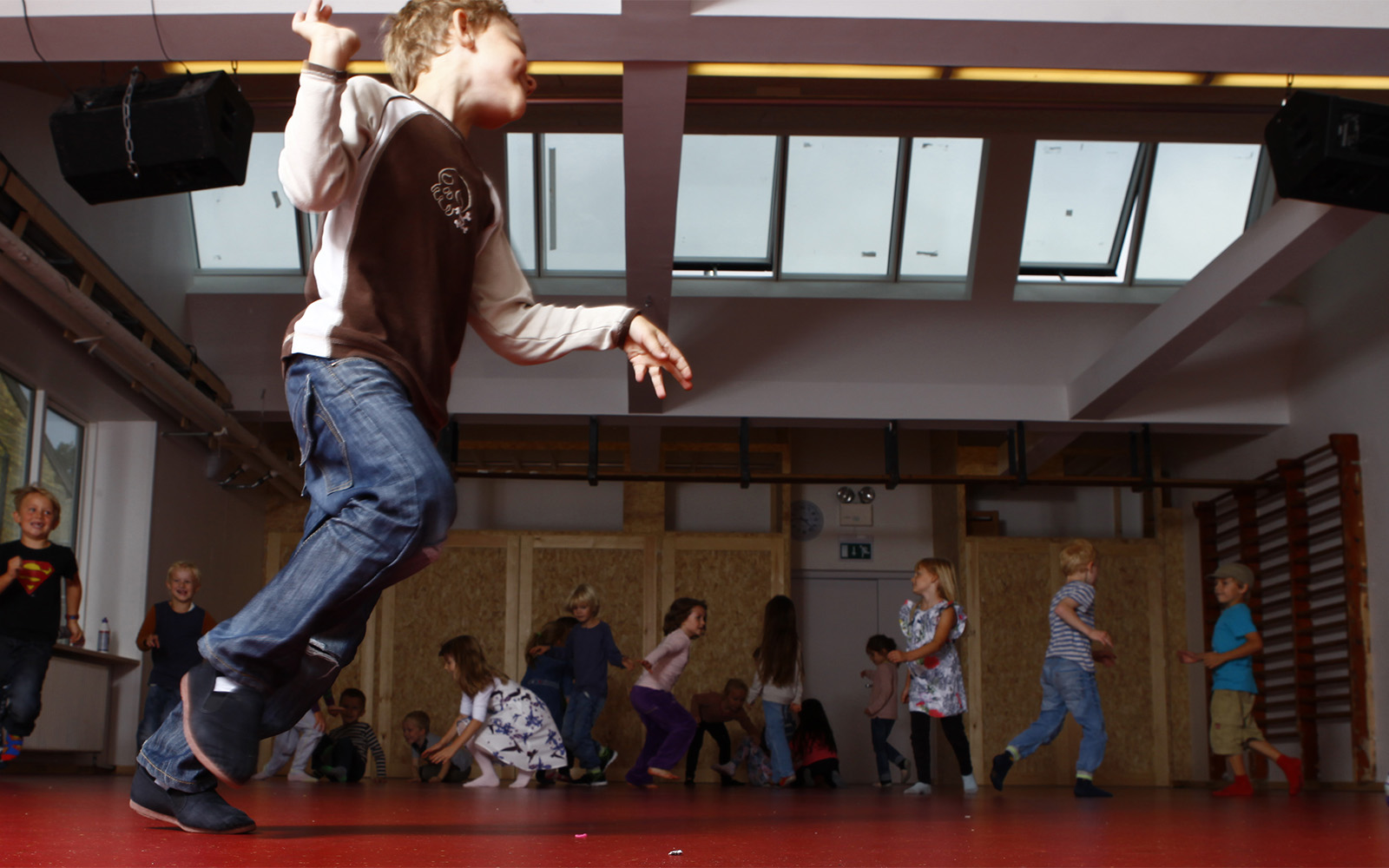 Young children playing in the school gym with roof skylights and roof ventilation